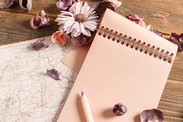 Blank notebook with flower on vintage wooden table
