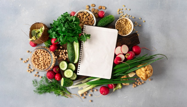 Blank notebook with fresh vegetables, herbs, legumes and nuts top view. veggie cooking concept