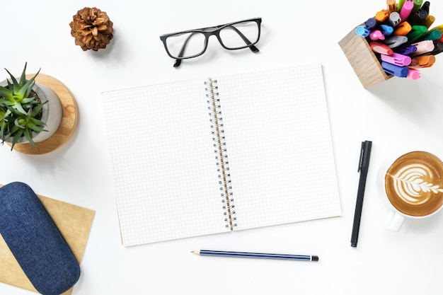 Blank notebook with grid lines is on top of white office desk table with supplies.