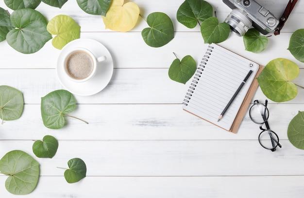 Пустой блокнот с зеленым листом в форме сердца и горячим кофе