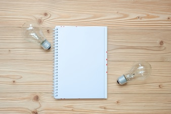 Blank notebook with lightbulb and crumbled paper on wooden table