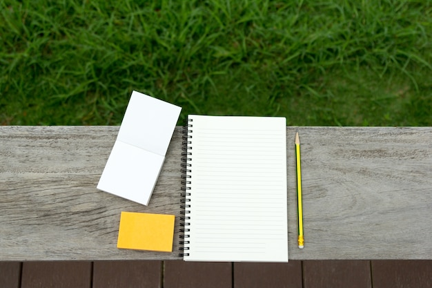 Blank notebook with notepad and pencil on wooden