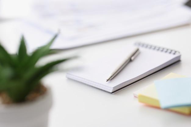 펜 및 컬러 스티커 빈 노트북 테이블 clloseup에 놓여 있습니다.