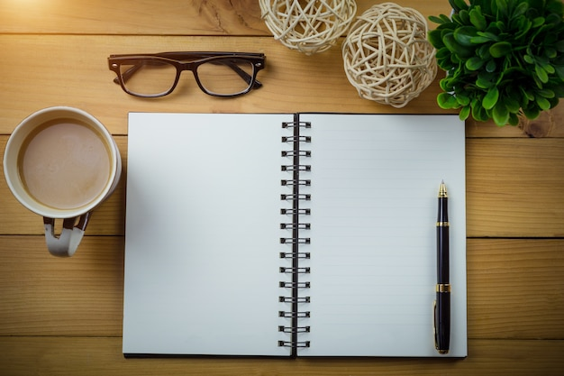 木製のテーブルにコーヒーのカップの隣に眼鏡とペンと空のノートブック