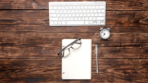 A blank notebook with a pen, glasses, an alarm clock are on the top of a wood office table