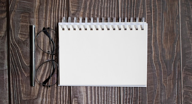 Blank notebook with pen,glasses on the wooden table, business concept