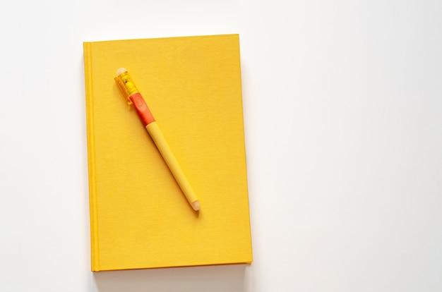 白い背景の上のペンで空白のノートブック