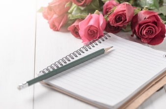 Blank notebook with pencil and red rose