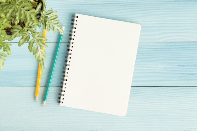 Blank notebook with and pencil on blue background
