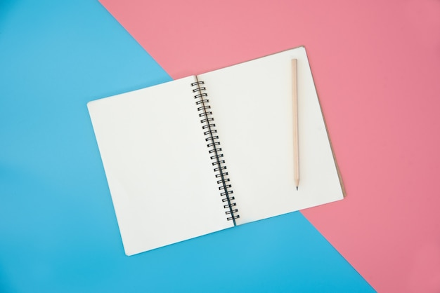 Blank notebook with pencil on color background