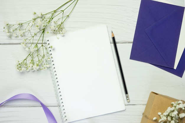Blank notebook with pencil on white wooden background. flat lay composition with free space for text.