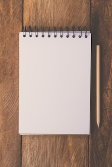 Blank notebook with pencil on wooden table