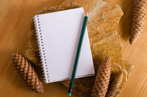 Blank notebook with pensil on wooden table and stone decorated with cones