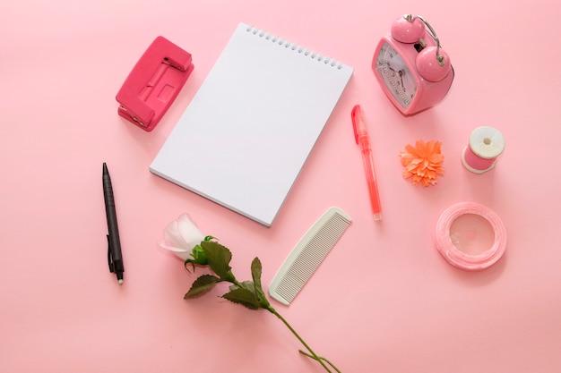 Пустой ноутбук с розовым weker, карандашом, розовым маркером, швейной нитью, белой расческой и белой розой