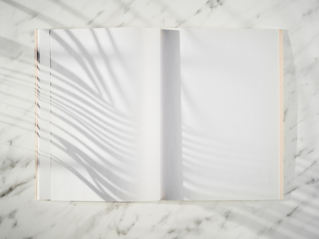 Blank notebook with shadows top view