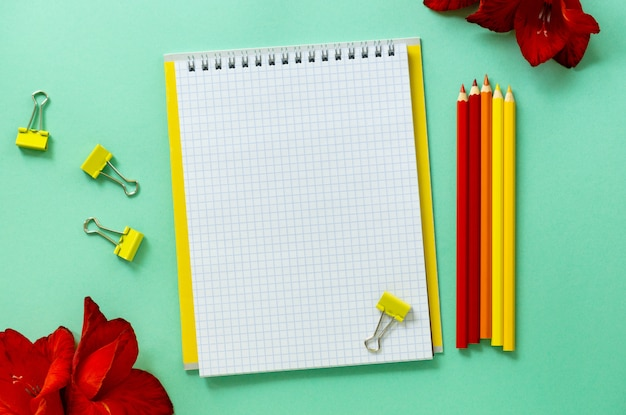 Blank notebook with stationery on a mint table