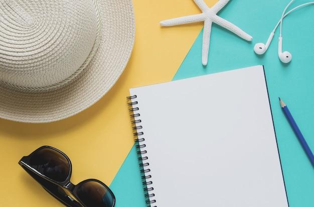 밀 짚 모자, 선글라스, starfishes, 연필, 이어폰, 노란색과 파란색 배경에 빈 노트북.