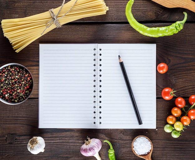 Blank notebook with white sheets, raw long paste and ingredients for cooking