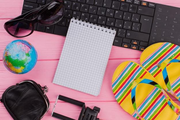 ピンクのテーブルトップの背景に女性の旅行者アクセサリーメガネ財布とビーチサンダルと空白のノートブック。グローブと黒のキーボード。