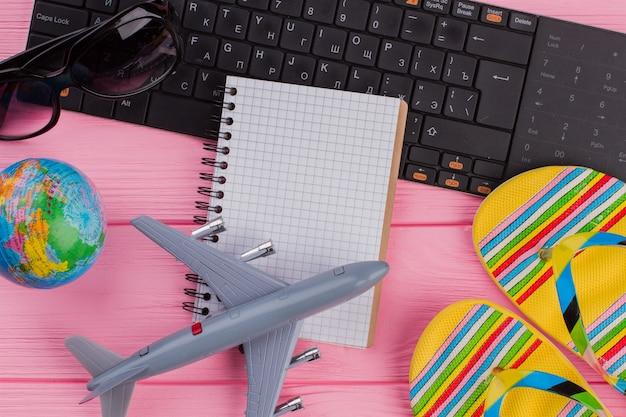 ピンクのテーブルトップのbackgに女性の旅行者のアクセサリーの眼鏡の財布とフリップフロップが付いている空白のノートブック...