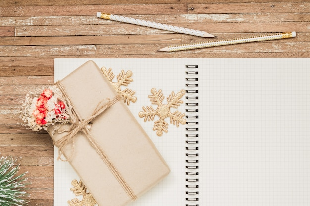 Blank notebook on wood with christmas ornaments and gift box