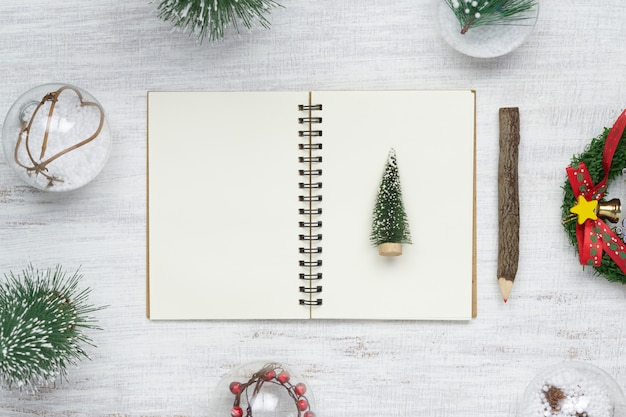 Blank notebook on wood with christmas ornaments.