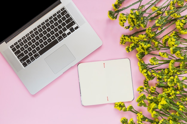 Blank notebook; yellow flowers and laptop on pink background