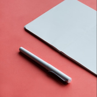 Blank notebookand pen isolated on background