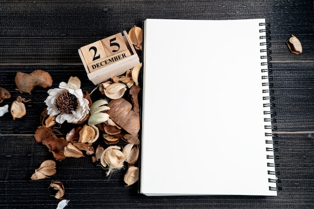 Blank notebooks are placed on a table with dried leaves and wooden block calendar