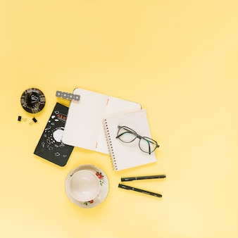 Blank notebooks; eyeglasses and pen with an empty cup on yellow background