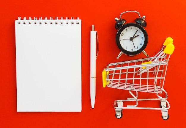 空白のメモ帳とペン、目覚まし時計、赤い背景のミニスーパーカート。オンラインショッピング、リスト、時間節約の概念。フラットレイ、上面図、コピースペース。