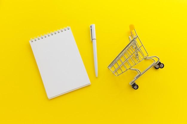 黄色の背景に空白のメモ帳とペンとミニスーパーマーケットカート。オンラインショッピング、リストのコンセプト。フラットレイ、上面図、コピースペース。