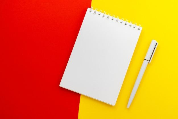トレンディな濃い黄赤色の背景に空白のメモ帳とペン。アイデアメッセージ、リスト、インスピレーションのためのノートブック。上面図、コピースペースのあるフラットレイ。