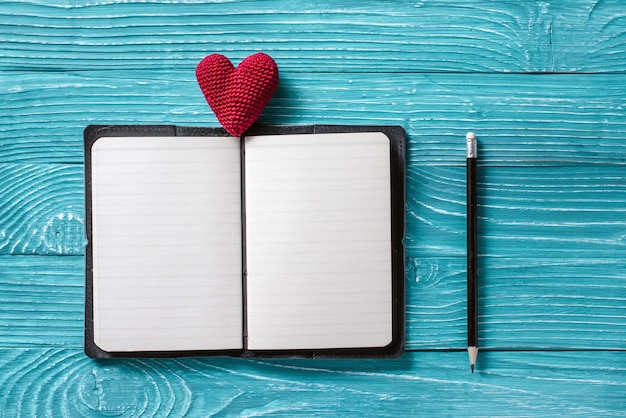 Blank notepad for copy space and vintage handmaded valentines day toy heart over light blue wooden background