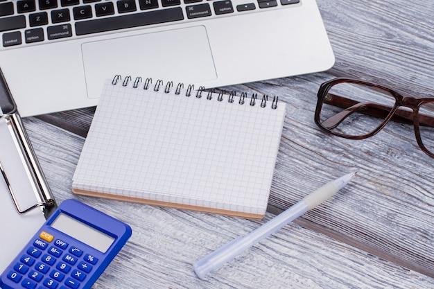Пустой блокнот для копирования космоса и финансов и предметов изучения. ноутбук с калькулятором и очками на белом деревянном столе.