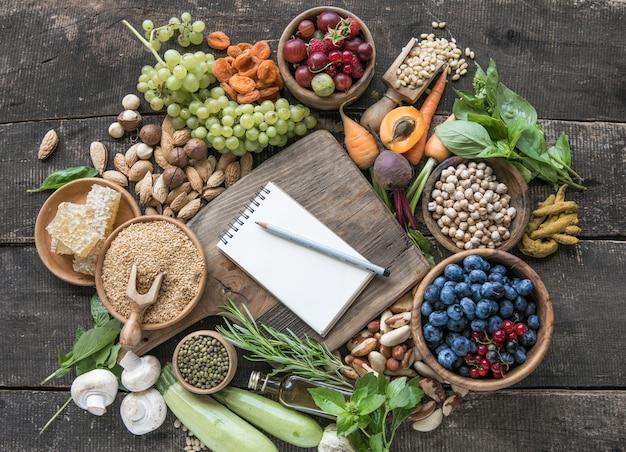 木製のテーブルのコピースペースと食材のための空白のメモ帳