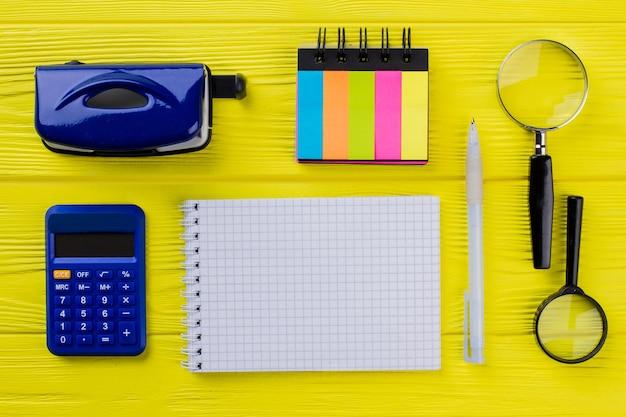 복사 공간을 위한 빈 메모장과 노란색 나무 테이블에 있는 복고풍 문구 사무용 액세서리. 평평한 평면도.