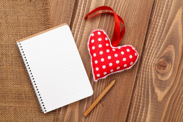 コピースペースと木製の背景の上のヴィンテージ手作りバレンタインデーおもちゃの心のための空白のメモ帳