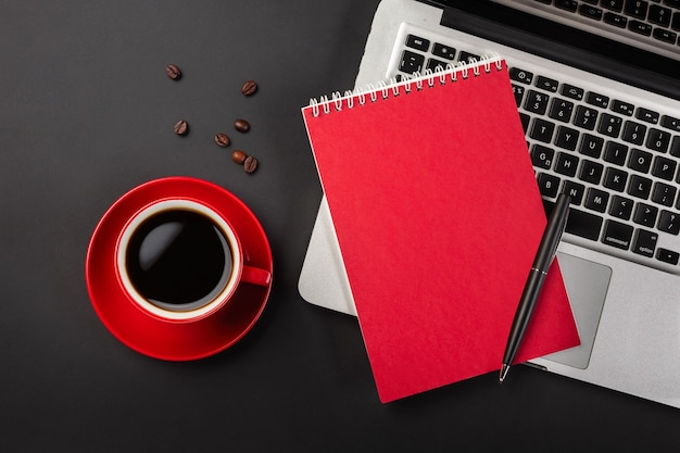 Blank notepad over laptop and coffee cup on office black table. top view with copy space.