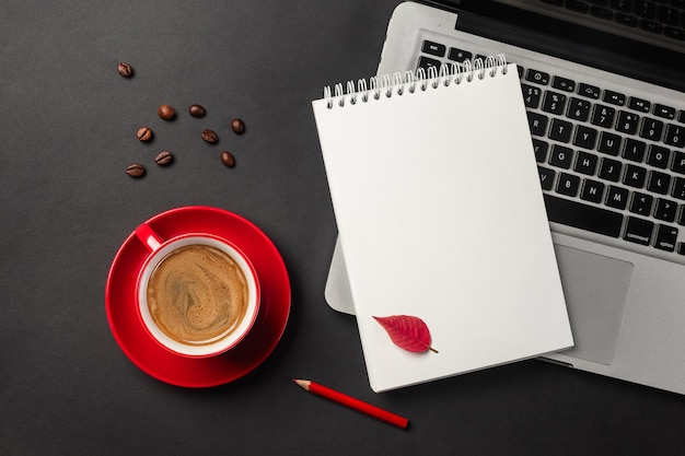 Blank notepad over laptop and coffee cup on office black table. top view.
