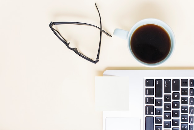 Blank notepad on laptop with eyeglasses and tea cup against beige backdrop