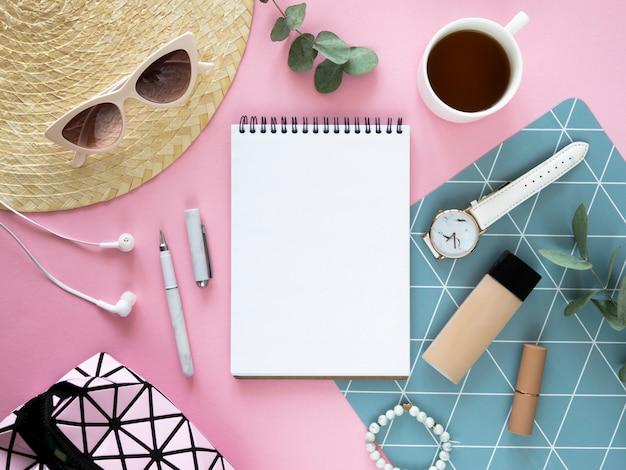 空白のメモ帳のモックアップ。化粧品、麦わら帽子、お茶、開いたメモ帳を備えたフラットな女性らしいピンクのデスクトップ。スペースをコピーします。