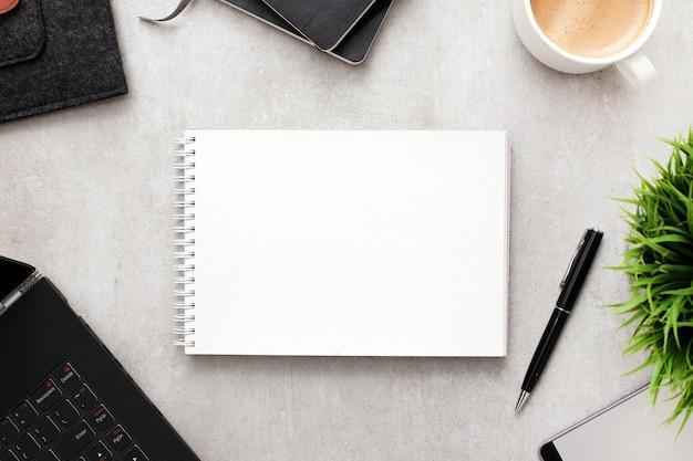 Blocco note o taccuino in bianco su area di lavoro con gli articoli per ufficio, vista superiore
