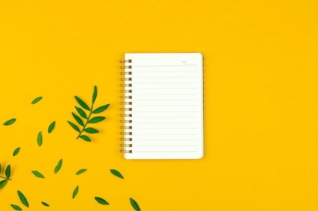 春の黄色の背景に空白のメモ帳、作業机または緑の葉のあるワークスペースのフラットレイ構成、写真