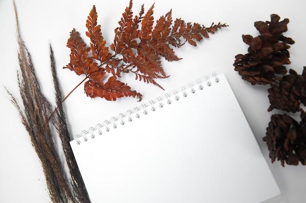 秋の植物組成物で飾られた白い背景の上の空白のメモ帳上面図フラットレイ