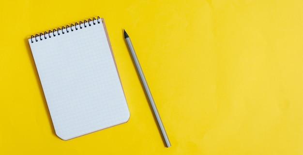 黄色のペンで黄色のスペースに空白のメモ帳。