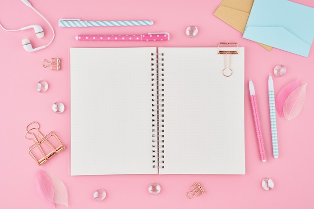 Blank notepad page in bullet journal on bright pink office desktop. top view of modern bright table