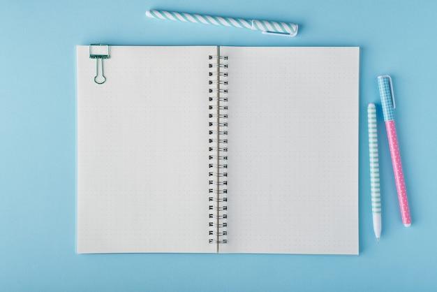 明るい青いオフィスのデスクトップの弾丸ジャーナルの空白のメモ帳ページ