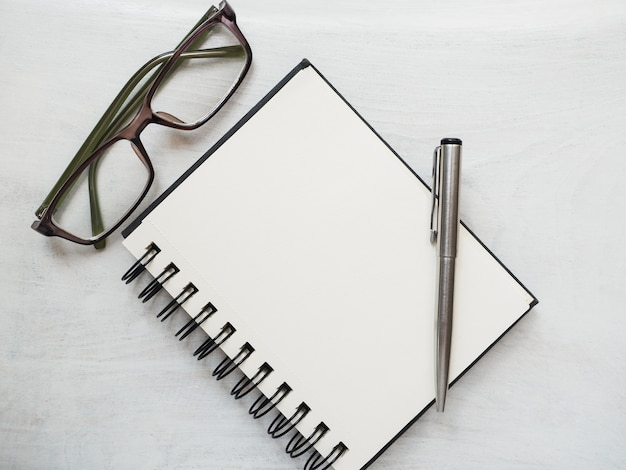 Blank notepad page, pen and glasses
