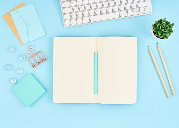 Blank notepad page for text on blue office desktop. top view of modern bright table  notebook